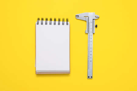 Calipers and blank page notepad on the yellow flat lay background. 免版税图像