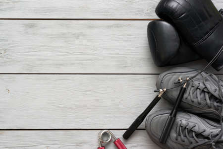 Boxing gloves, sport shoes and jumping rope on a wooden flat lay background with copy space.