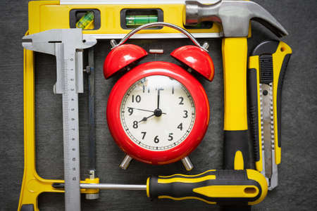 Red alarm clock and work tools on the table. Repair time abstract background. 版權商用圖片 - 152886960