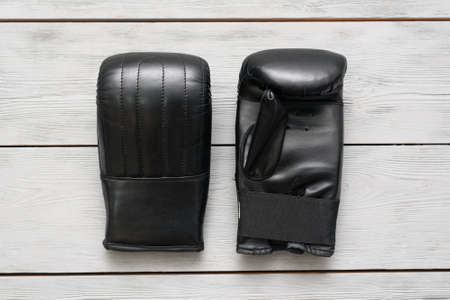 Pair of black leather boxing gloves on the wooden floor background. 版權商用圖片