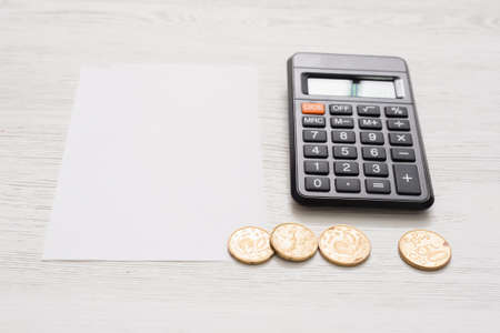 Calculator, cent coins and blank paper page on the white table background.