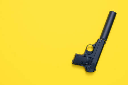 Black airsoft gun on yellow flat lay background. 版權商用圖片 - 152886968