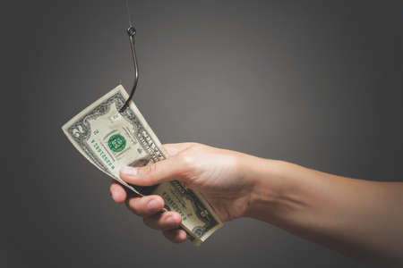 Human hand is holding a dollar on the fishing hook close up on gray background.