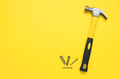 Hammer and heap of nails on the yellow flat lay background with copy space. 版權商用圖片 - 152886971