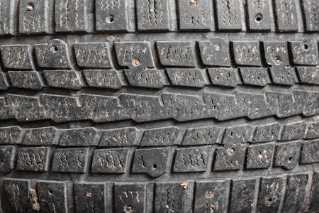 Worn out tread on studded tires of car background. 版權商用圖片