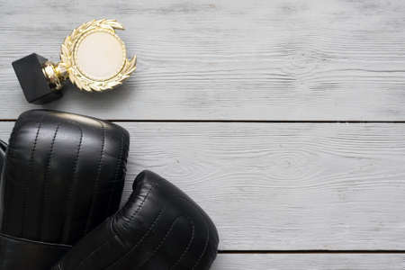Boxing gloves and golden award trophy medal on the gray flat lay background with copy space.