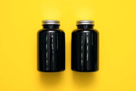 Black plastic jars on the yellow flat lay background. 版權商用圖片