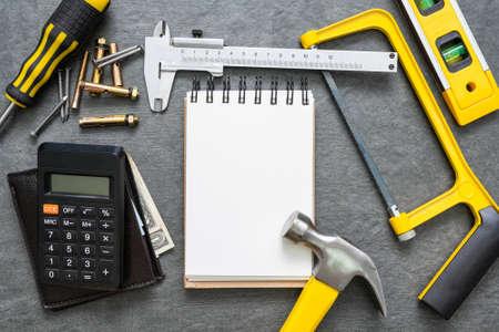 Construction cost or repair calculation mockup. Blank page notepad and work tools on the workbench. 免版税图像
