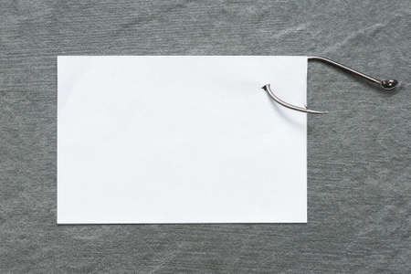 Blank paper page on the fishing hook on the table flat lay background. To do list.