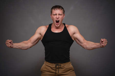 An angry man is yelling and shaking his fist on gray background. 스톡 콘텐츠