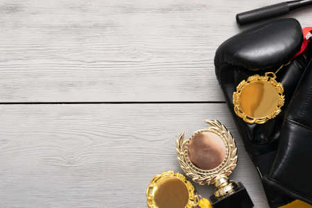 Boxing gloves and golden award trophy on the gray flat lay background with copy space.