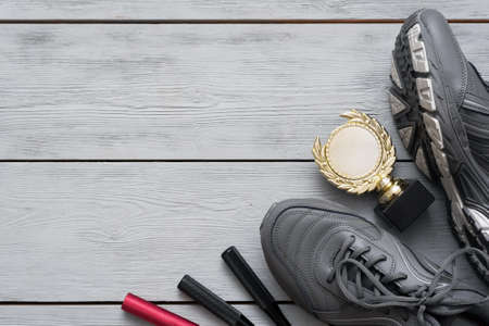 Sport shoes and golden award trophy on the wooden flat lay floor background with copy space. 免版税图像