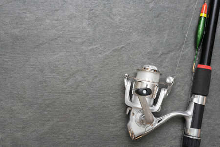 Fishing rod with reel on gray flat lay background with copy space.