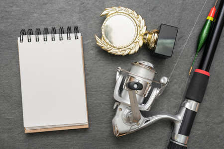 Fishing rod, blank page notepad and golden award trophy on the gray flat lay background. 免版税图像