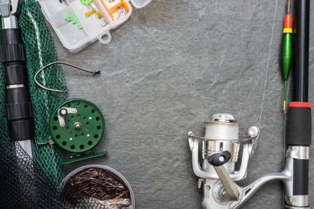 Fishing rod with reel on gray flat lay background with copy space. Fishing accessories on the table.