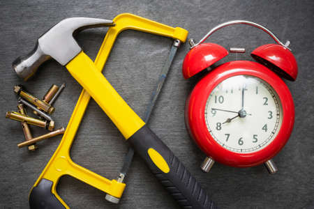 Red alarm clock and work tools on the table. Repair time abstract background. 版權商用圖片 - 152888976