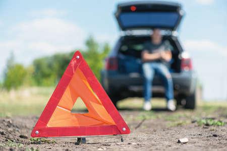 Warning triangle sign and broken car.