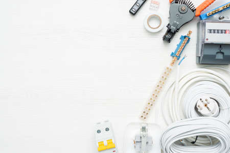 Electrical equipment and accessories on the white workbench background with copy space.