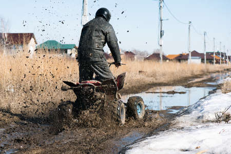 Motor biker is riding a quad bike on the dirty road.