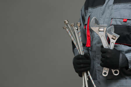Plumber with adjustable wrenches and water hoses on a gray background with copy space.