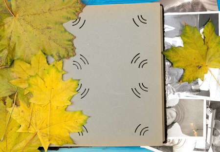 Open vintage photo album book with blank pages and with copy space for image or for text laying in fallen autumn leaves and retro photos of peoples with no faces on wooden table surface background.