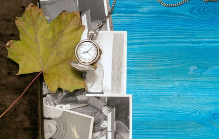 Vintage photo album book and retro pocket watch laying in fallen autumn leaves and retro photos of peoples with no faces on wooden desk table surface background. Photo album background mockup design.