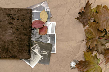 Vintage photo album book and pocket watch laying in fallen autumn leaves and retro photos of peoples with no faces on crumpled paper page surface background. Photo album background design.