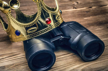 VIP premium search. Binoculars and golden crown on wooden desk table background. In searhing for something special. Stockfoto