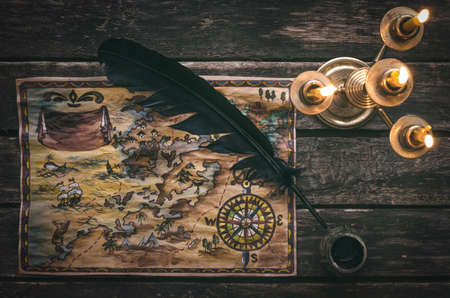 Pirate treasure map, burning candle, feather pen and inkwell on wooden ship table background. Stock Photo