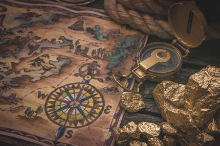 Treasure map, compass and gold nuggets on the table. Gold hunting concept.