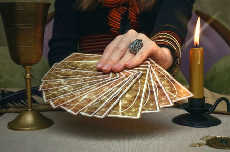 Tarot cards on fortune teller desk table. Future reading. Woman fortune teller holding in hands a deck of tarot cards.