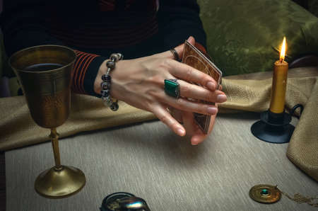 Tarot cards on fortune teller desk table. Future reading. Woman fortune teller holding in hands a deck of tarot cards and shuffles it.