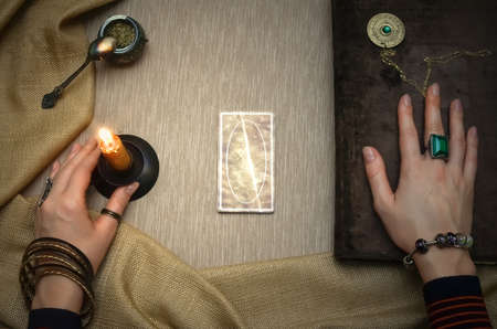 Book of magic. Tarot cards on fortune teller desk table. Future reading. Woman witch reads a ancient magic scroll book and learn art of prediction on wooden table. 写真素材