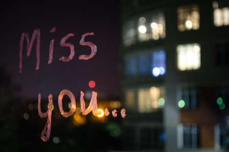 Miss you, inscription (text) by lipstick on the window glass in the night. Love and miss concept. Valentine background.