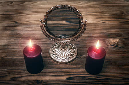 Golden mirror on the magic table between a two burning candles on both side on wooden desk table background. Future reading.