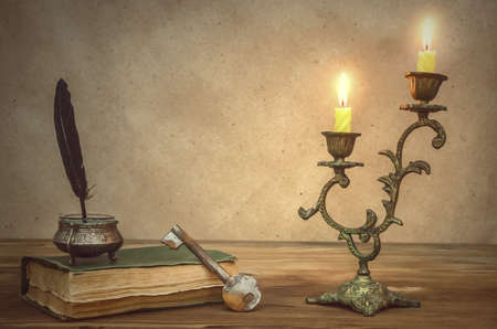 Old book and feather pen with inkpot and rusty key on retro wooden table background in the light of burning candle. Education. Back to school. Memoirs. Writer table concept. Vintage background.
