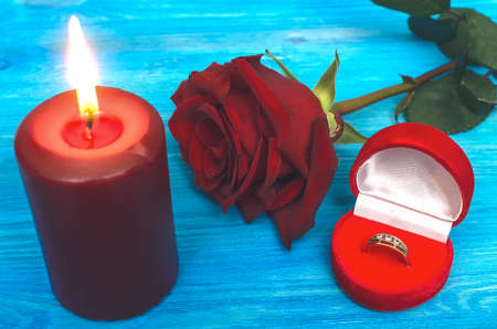 Wedding ring in a gift present box red rose flower and burning candle on wooden table background. Marriage offer romantic background. The proposal concept. 版權商用圖片