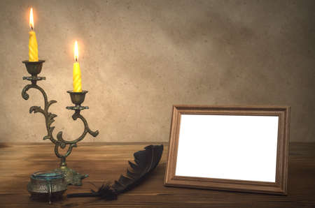 Empty photo frame with copy space burning candle in vintage candlestick and feather pen with inkpot on retro wooden table background. Writer table concept. Education.