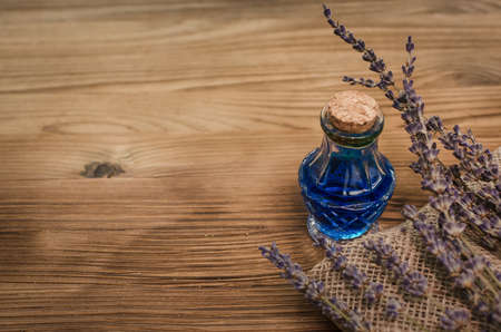 Herbal medicine. Alternative medicine concept. Dry organic natural ingridients. Healing tincture beverage and dry lavender branches on the table.