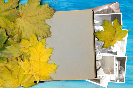 Open vintage photo album book with blank pages and with copy space for image or for text laying in fallen autumn leaves and retro photos of peoples with no faces on wooden table surface background. Foto de archivo