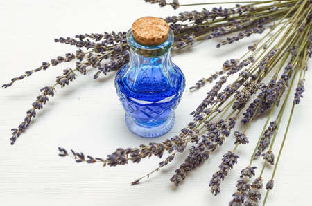 Dry lavender branches and bottle with blue medical tincture on white wooden background. Herbal medicine concept. Alternative medicine.