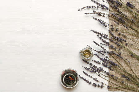 Dry lavender branches and herbal collection on white wooden background with copy space. Herbal medicine concept. Alternative medicine. Standard-Bild