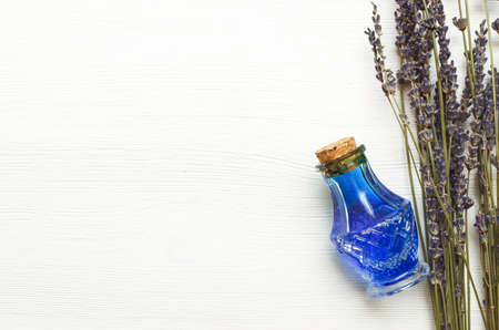 Dry lavender branches and bottle with blue medical tincture on white wooden background with copy space. Herbal medicine concept. Alternative medicine.