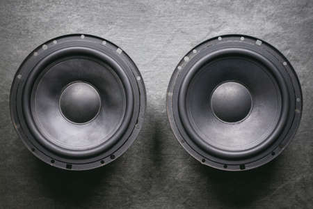 A car audio loudspeaker on dark flat lay background.