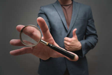 Magnifying glass in the businessman hand close up on gray background. Фото со стока