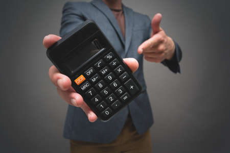 Calculator in businessman hand close up on gray background.