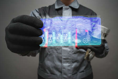 Car engine diagnostic concept. Car mechanic holding in hands a digital tablet with charts.