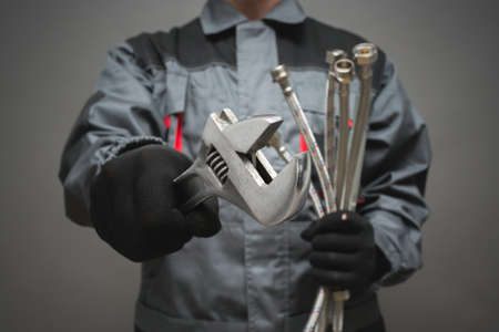 Plumber with adjustable wrench and water hose pipe close up.