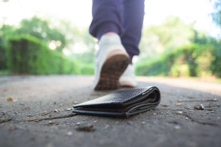 Lost wallet on the road and walking away woman.