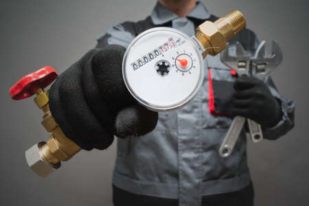 Water meter and adjustable wrench in plumber hands close up.